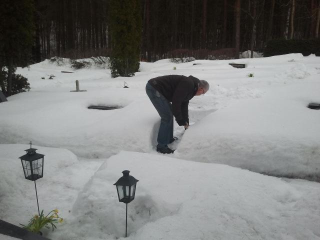 Maken röjer snö från sin farmors och farfars grav.