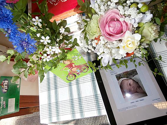 Blommor som maken fick igår då han fick sitt första barnbarn. Det lilla flickebarnet syns på bilden, uppskattningsvis inte mer än en timme gammal.