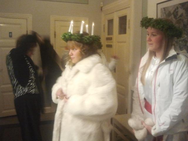 Johanna Österholm har krönts till lucia på rådhusets balkong. Nu klär hon sig i varm päls. Till höger en av de tre tärnorna, Klara Fält.