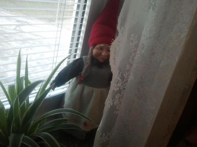 Tomtemor gluttar fram bakom gardinen i gästrummet där vi bor.