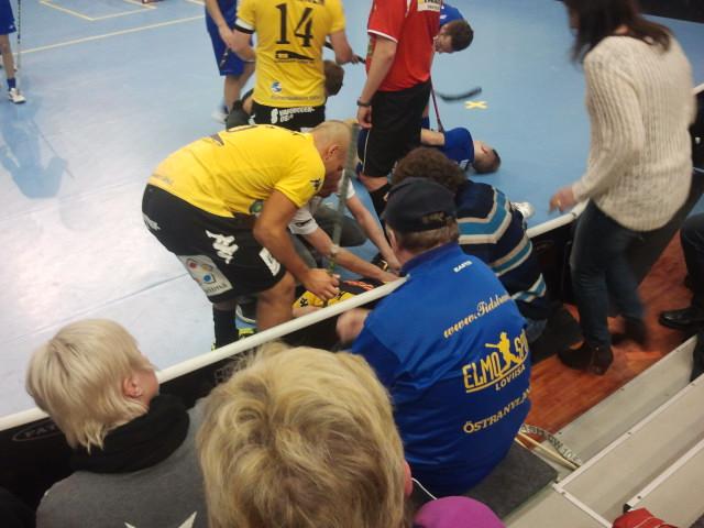 Innebandy är ett snabbt spel och ibland smäller det till. Rasmus Horn, som inte syns på bilden, har tacklats och ligger lite groggy vid sargen. Deina Imjack kollar läget.