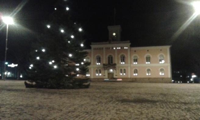 I väntan på bussen. En kur finns på torget. Det här är vårt rådhus och stadens julgran.
