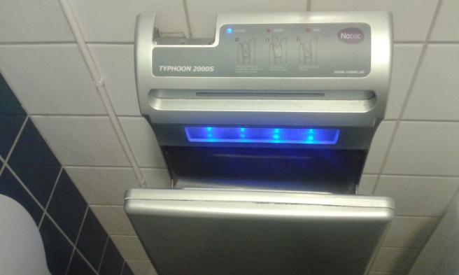Ner i  den här ska man våga stoppa händerna om man vill att de ska torka efter att man tvättat dem på allmänna toan.