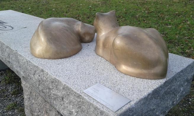 Katter vilar på en bänk. Konst i en park invid Eskilstuna å.