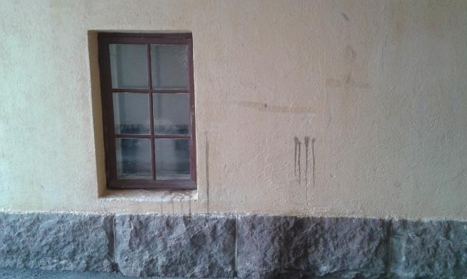 Fönster, vägg och stenfot i samma portgång.