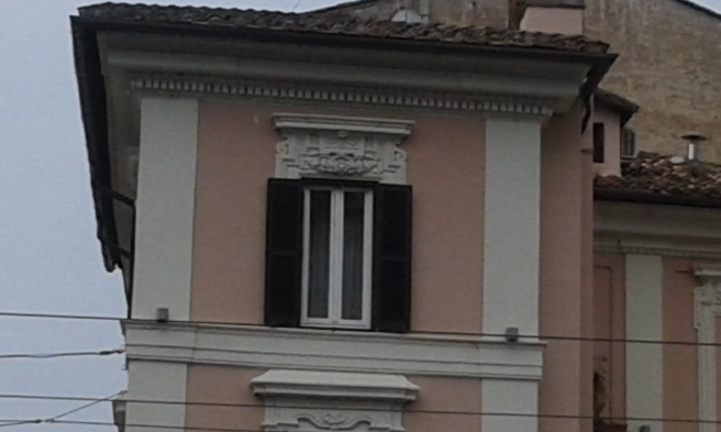 Från det här fönstret har någon direkt utsikt över Colosseum. Fönsterluckor finns det gott om i Rom, och ofta även utsmyckningar bredvid och/eller ovanför fönstren.