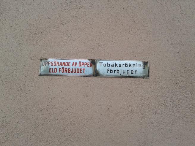 Skyltar på en vägg på Alexandersgården.