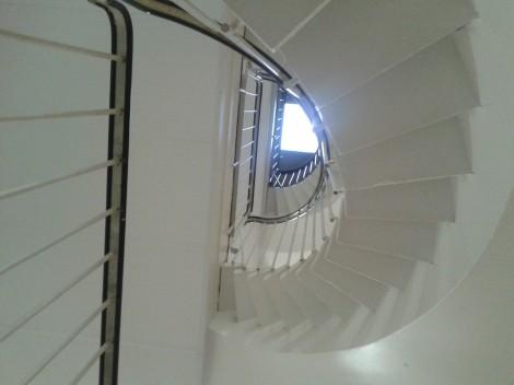 Står på bottenvåning i huset där jag bor och kikar upp mot takfönstret i tredje våningen.