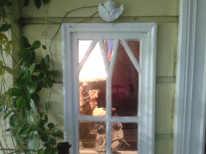 Ett litet fönster på verandan, som ger insikt i husets hall.
