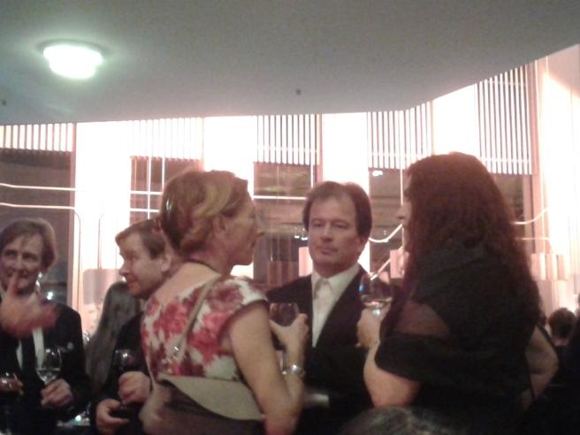 Författaren Kjell Westö samtalar med två damer.