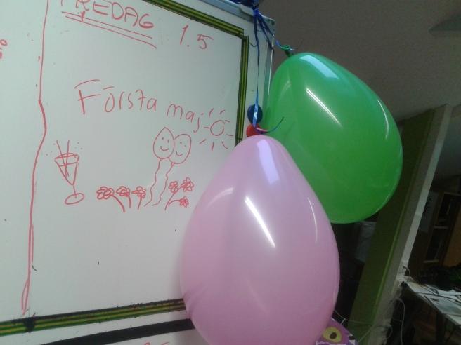 Påminnelse om första maj på whiteboarden på jobbet och ballonger inför valborgsmässoafton.