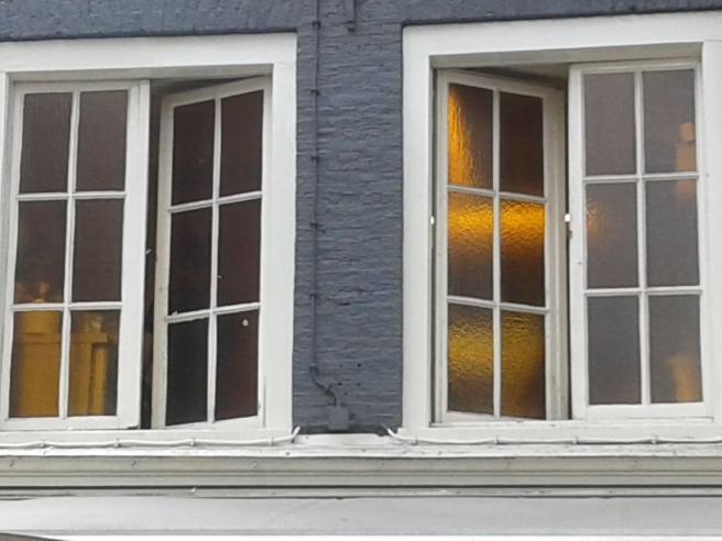 Under en kvällspromenad i Amsterdam såg jag de här fönstren. Sekunden innan jag knäppte bilden visade sig en kille i det öppna fönstret.
