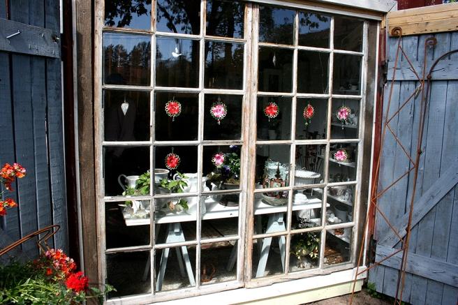 Försäljningsbodens fönster hos Olga och Markku i Konungsdammens trädgård.