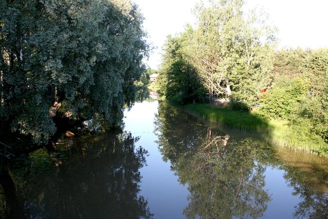 Så vackert hus och träd speglar sig i den stilla Illby ån.