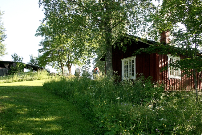 En annan stuga på Postbacken. Till vänster syns en del av byggnaden där scenen och publikens sittplatser finns.