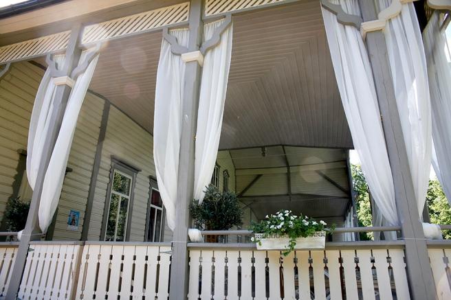 En eftermiddagens bris fladdrar spetsgardinerna på den öppna terrassen så fint.