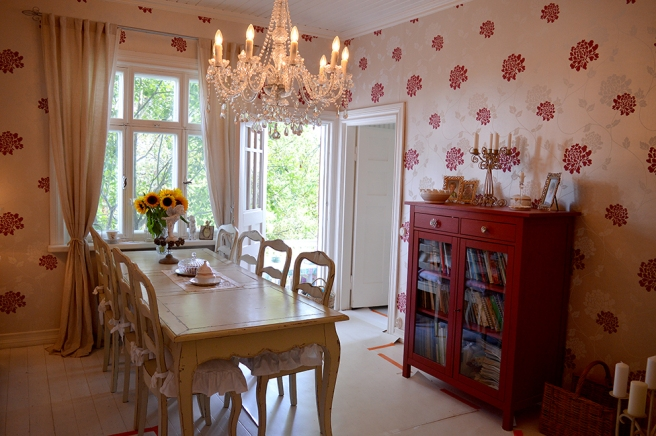 En romantisk matsal med dörren till terrassen öppen.