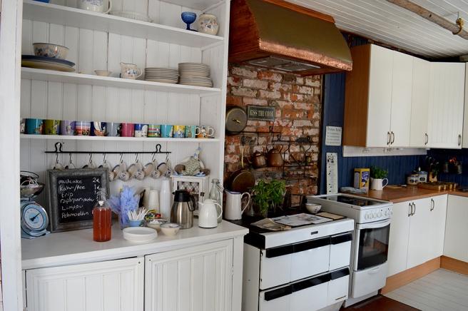 Ett stort, ljust och på alla sätt inbjudande kök med vacker tegelvägg.
