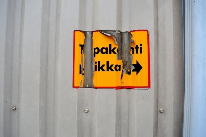 Tror att här ska stå Tupakointi paikka och pilen visar till höger. Plats för rökning bakom hörnet alltså.