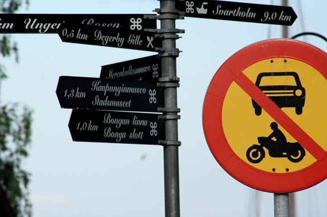 Gillar kontrasten mellan de svartvita små skyltarna och det granna förbudsmärket.